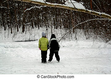 Hand in Hand Skate - Two young kids skate on natural outdoor...