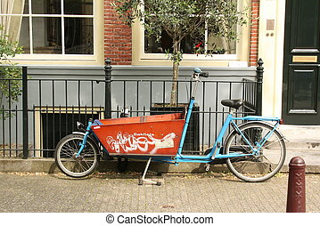 Tricycle against a facade of a house in Amsterdam.The...