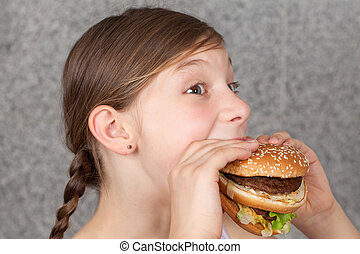 Girl eating a hamburger - Young girl eating a fast food...
