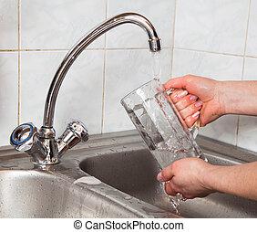Washing of a beer glass - woman hands rinsing a beer glass...