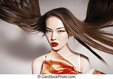 Photo of beautiful asian woman with magnificent hair. Fashion photo