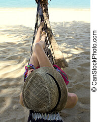 Slim young woman in a hammock wearing straw hat