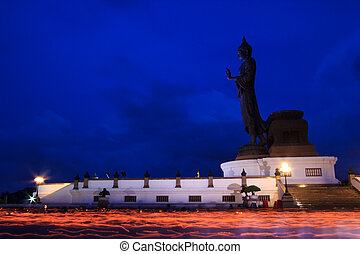 lighted candles in hand around buddha statue - Walk with...
