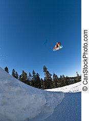 Into the blue - Snowboarder going off a big jump.