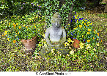 buddha statue in sitting position under a cherry tree