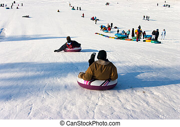 Winter amusement - Tobogganing from a hill in winter park