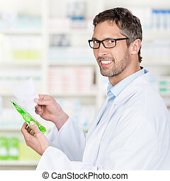 Pharmacist Holding Prescription Paper And Product In...