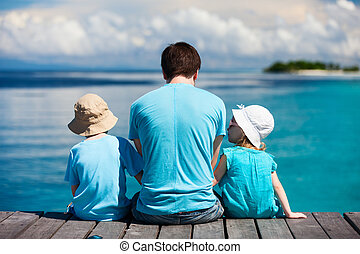 Father and kids enjoying ocean view - Back view of father...