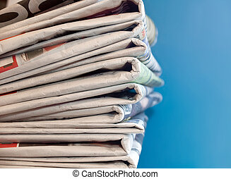 Newspapers - A stack of old newspapers with a blue...