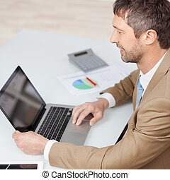 Businessman Working With Laptop At Desk - High angle view of...