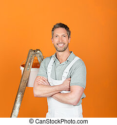 Smiling Painter With Arms Crossed Standing Against Orange Painted Wall