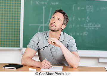 Thinking Teacher In Classroom - Thinking male teacher at...