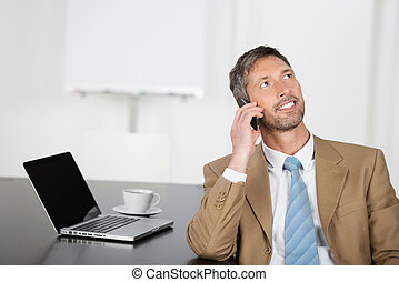 Businessman Using Mobile Phone While Looking Up At Desk -...