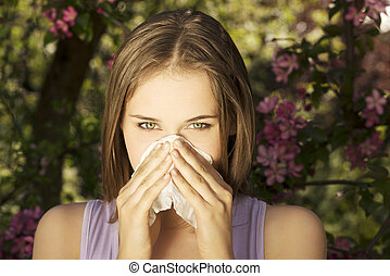 Young woman with allergy during sunny day is wiping her nose...