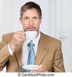 Businessman Enjoying Coffee In Office - Mature businessman...