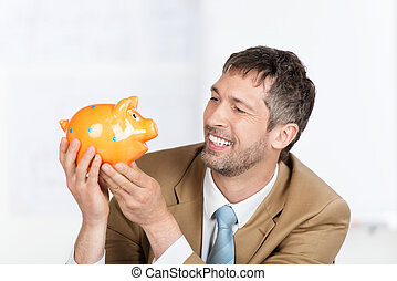 Businessman Holding Piggybank In Office - Happy mature...