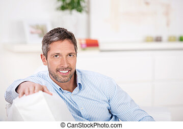Mature Man Sitting On Sofa - Portrait of mature man sitting...