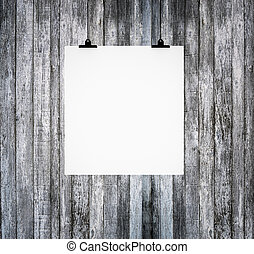 Blank paper board hanging on grunge wooden wall