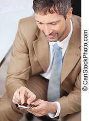 Businessman Using Mobile Phone In Office - High angle view...