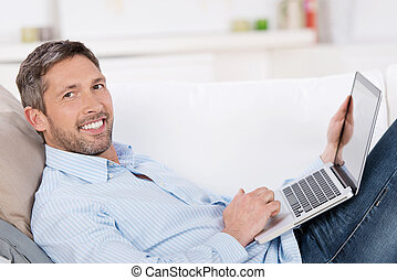 Mature Man Holding Laptop On Sofa - Portrait of happy mature...