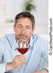 Mature Man Testing Wine At Home - Portrait of happy mature...