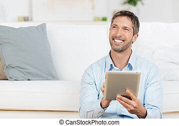 Man Holding Laptop While Looking Away In House - Portrait of...