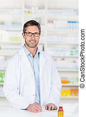 Male Pharmacist At Pharmacy Counter - Mature confident male...