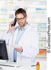 Pharmacist Using Phone At Counter - Mature male pharmacist...