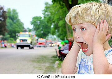 Child Covering Ears at Loud Parade - A young blonde boy...