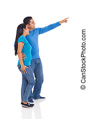 indian couple pointing at empty copy space - cheerful indian...