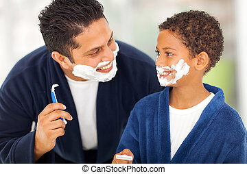 playful father and son shaving together at home bathroom
