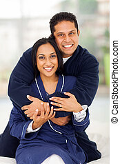 happy indian couple hugging on bed at home