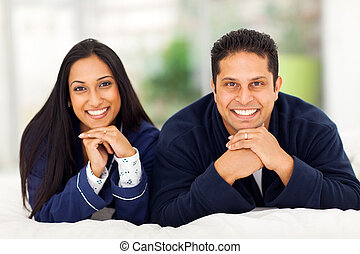 happy indian couple lying on bed - portrait of happy indian...