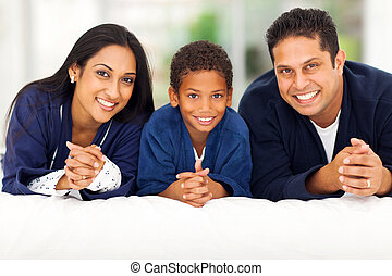indian family lying on bed together - cheerful indian family...