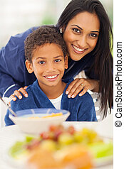 mother and son at breakfast table - close up portrait of...