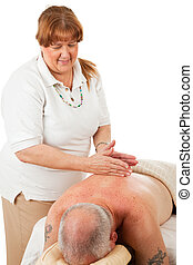 Massage Therapy - Masseuse giving a massage to a relaxed,...