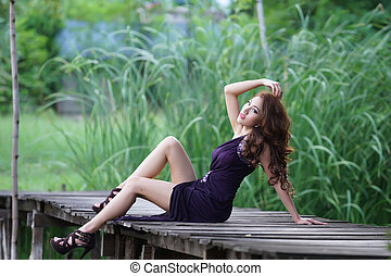 Young Asian woman posing in greenery background - Young...