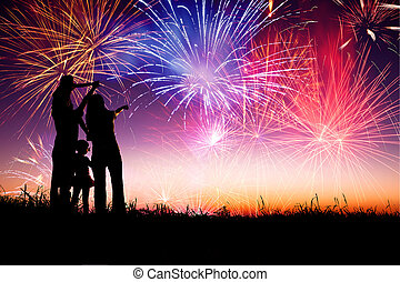 happy family standing on the hill and watching the fireworks...