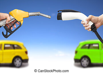 electric car and gasoline car concept hand holding gas pump...