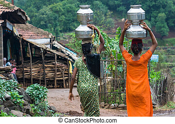 Villagers Carrying water - Villagers carry water in a remote...