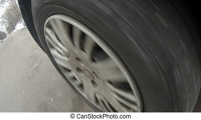 Moving car wheel on asphalt