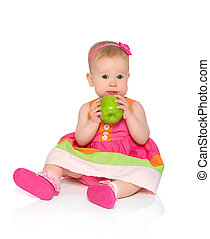 happy little baby girl in bright multicolored festive dress with green apple isolated on a white background