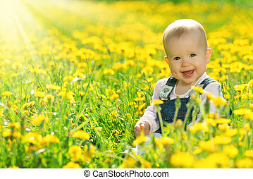 happy baby girl on  meadow with yellow flowers  on the nature