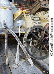 Arrangement of vintage items - Wagon wheels, metal barrel,...