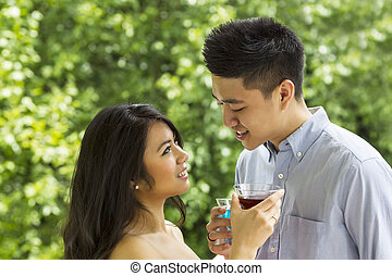 Young Adult Couple sharing a drink with each other outdoors