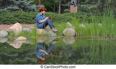 Girl read e-book on the pond - Red-haired girl sitting on...