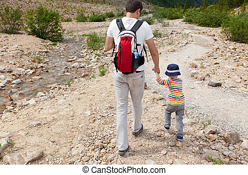 family hiking - young caucasian father and his son hiking in...