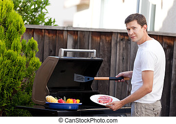 man grilling food - young handsome man ready for grilling...