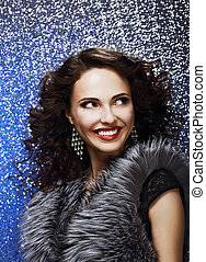 Sparkle. Beautiful Fashion Model with Shiny Earrings in Fur Vest. Toothy Smile