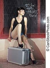 woman sits on suitcase in ancient city